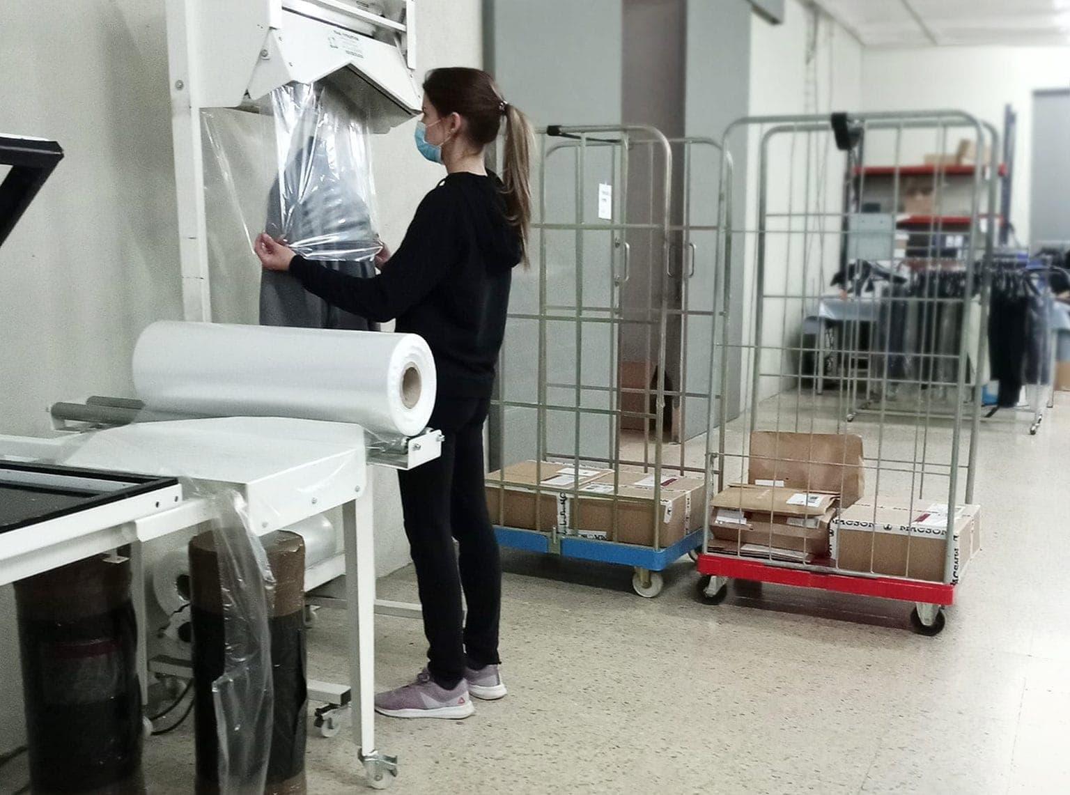 Mujer embalando un traje en un almacén de logística de un ecommerce de moda.